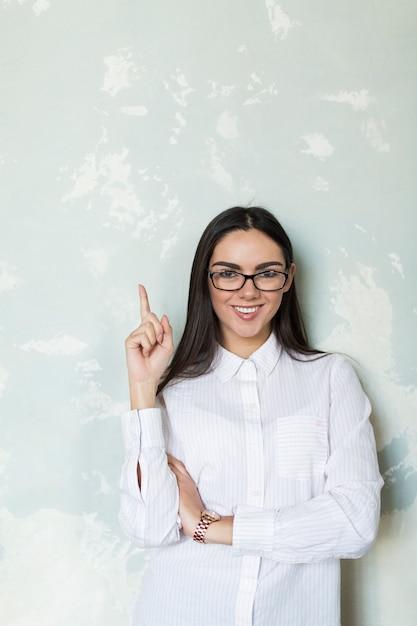 Smart girl having idea pointing up Free Photo