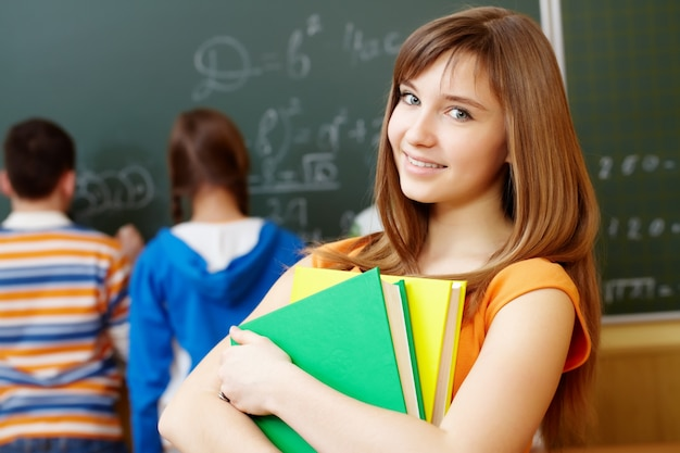 Smart girl holding books in the classroom Free Photo