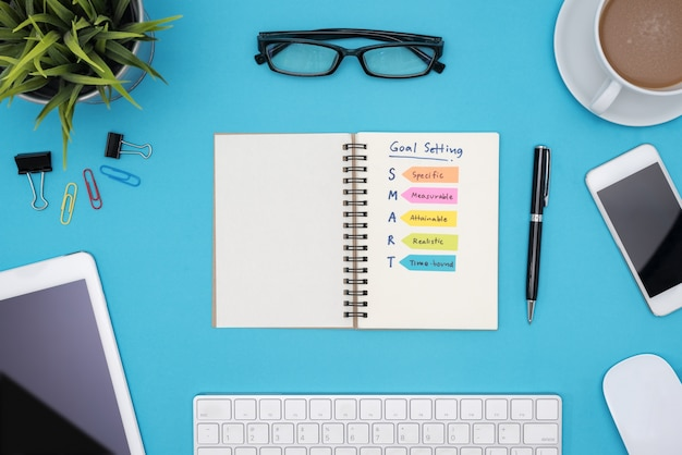 Smart goal setting with office supplies over blue desk Free Photo