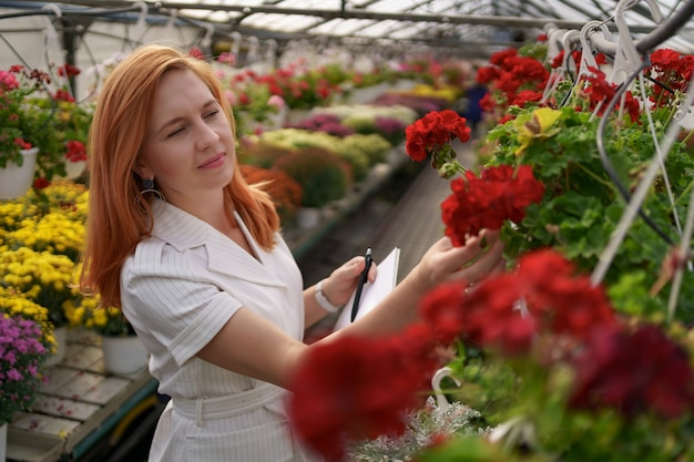 スマート温室制御。女性労働者は日光の下で赤い花を検査し、データを記録します 無料写真