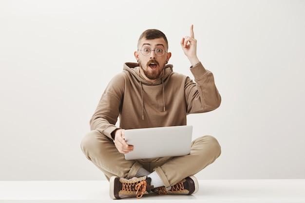 Умный парень сидит с ноутбуком, имеет отличную идею, делится предложением Бесплатные Фотографии