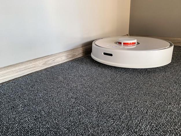 Smart house. vacuum cleaner robot runs on floor in a living room. Premium Photo