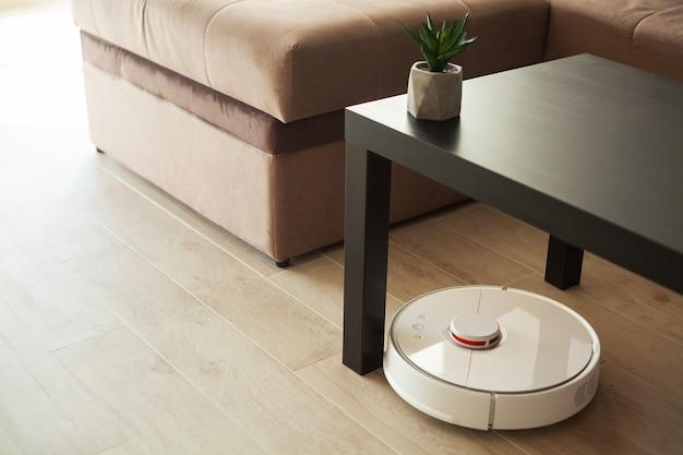 Smart house. vacuum cleaner robot runs on wood floor in a living room Premium Photo