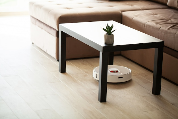 Smart house, vacuum cleaner robot runs on wood floor in a living room Premium Photo