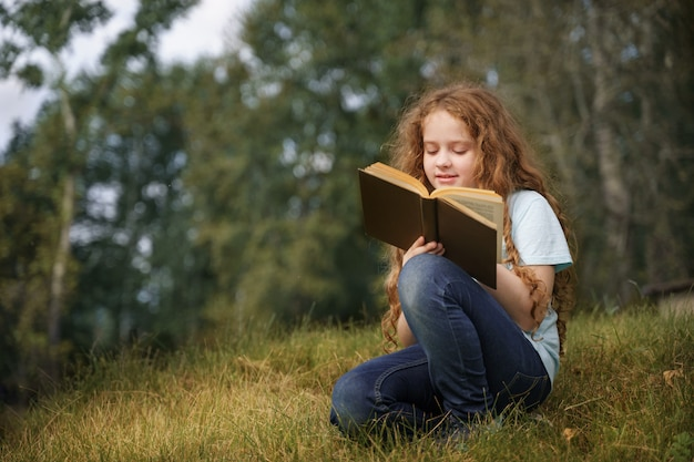 Smart little girl reading the book outdoors. Premium Photo