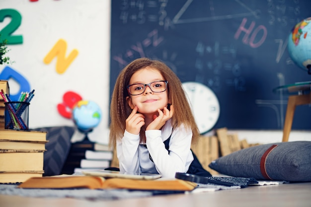 Smart little schoolgirl with digital tablet in a classroom. Premium Photo