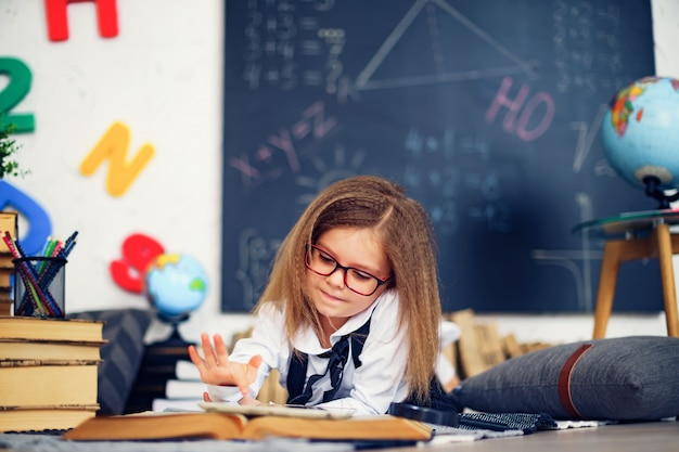 Smart little schoolgirl with digital tablet in a classroom. Premium Photo