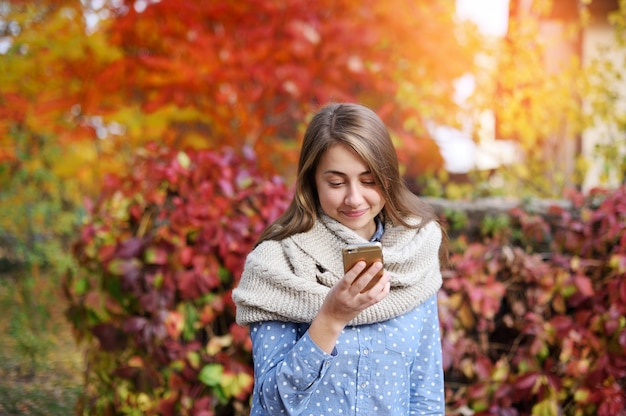 Smart phone autumn woman writting sms on mobile phone in fall Premium Photo