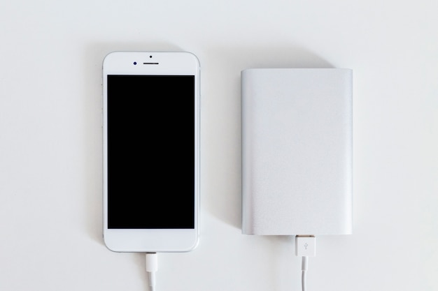 Smart phone connected with power bank charger over the white background Premium Photo