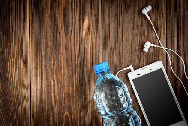 スマートフォン、ヘッドフォン、木製のテーブルの上に水のボトル。 Premium写真