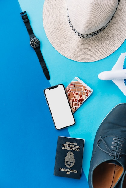 Smart phone; map; passport; toy airplane; shoes; wrist watch and hat on dual background Free Photo