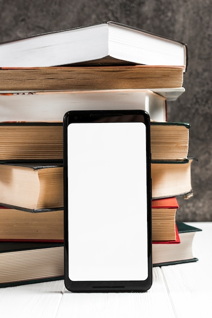 Smart phone with white screen in front of vintage stacked books Free Photo