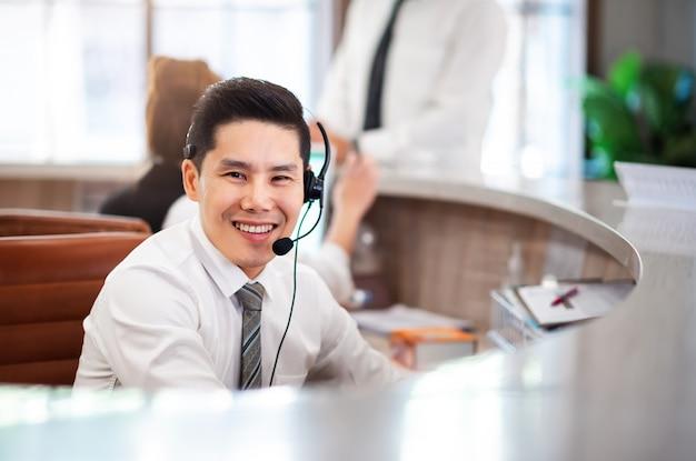 コールセンター部門のオペレーターで笑顔のスマートプロのアジア人。 happy service mind telecommunication departmentとの協力 Premium写真