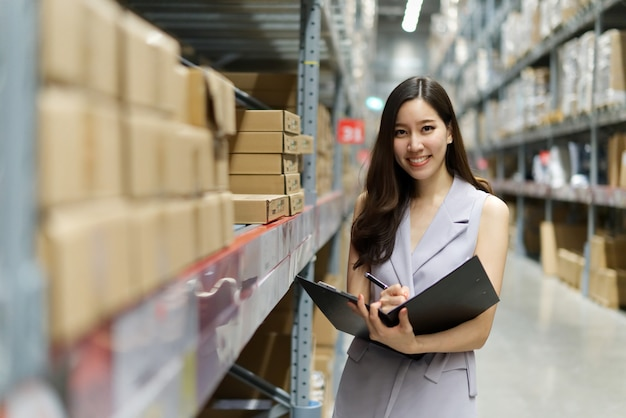 Smart smiling asian woman working in store warehouse. Premium Photo