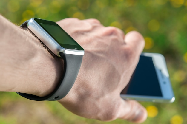 Smart watch on the hand that holds the phone. Premium Photo