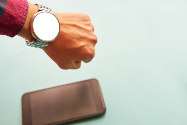 Smart watch on hand with isolated, blank screen for mockup and smartphone on the table on Premium Photo