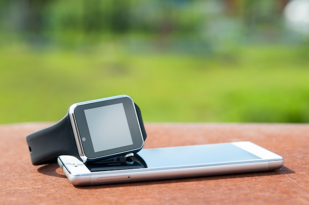 Smart watches are on the phone, on the background of nature. Premium Photo