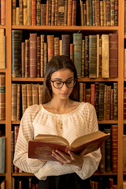 Smart woman reading book in library Free Photo