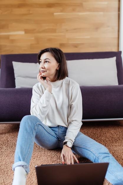 Умная женщина работает на ноутбуке, сидя на полу дома в дневное время одет Бесплатные Фотографии