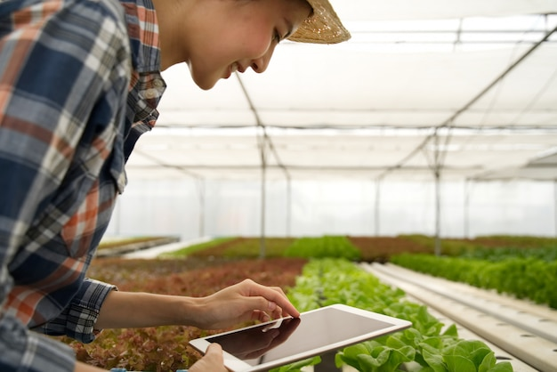 Smart young cute asian farmer girl using tablet to check quality and quantity of vegetable in hydroponic farm Premium Photo