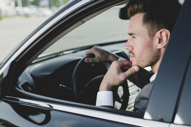 車でスマートな若いハンサムな男 無料写真
