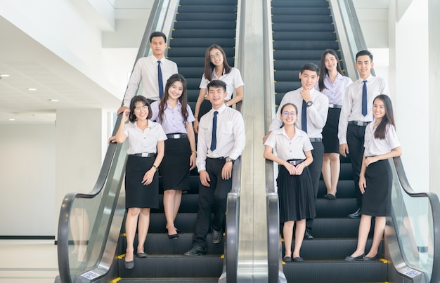 Smart young students standing together on escalator Premium Photo