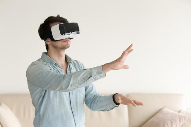 仮想現実の眼鏡、smartp用のvrヘッドセットを着ている若い男 無料写真