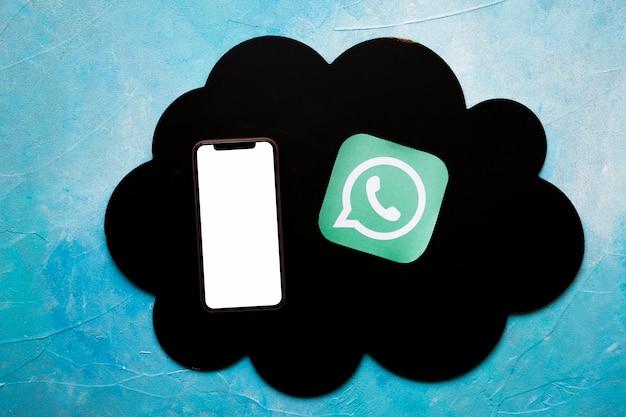 Значок смартфона и мультимедиа на черном облаке над окрашенной синей стеной Бесплатные Фотографии