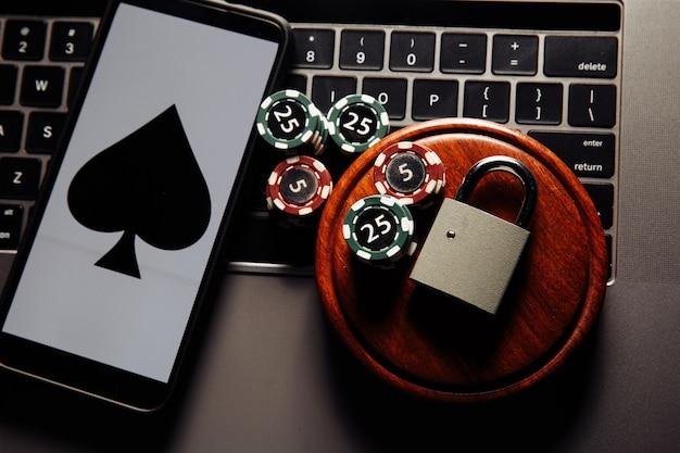 スマートフォンと南京錠、ポーカーチップ、ノートパソコンのキーボードのトランプ。法の概念とギャンブルの規制 Premium写真