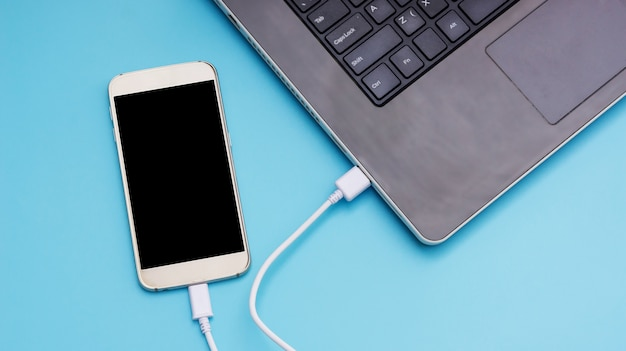 Smartphone connecting to a laptop on a blue background. Premium Photo