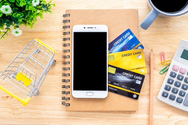 Smartphone on credit cards,notebook,flower pot tree,shopping cart,calculator and coffee cup on wooden background,online banking top view office table Premium Photo