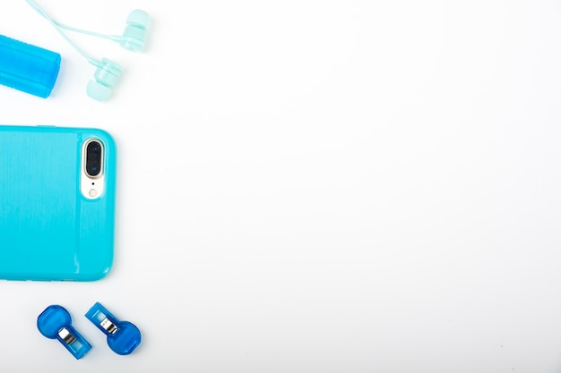 Smartphone; earphone and whistle on white surface Free Photo
