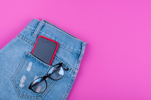 Smartphone in front jeans pocket with eye glasses and algeria coin money Premium Photo