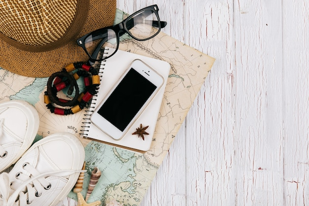 Smartphone lies on a notebook beforeon the map, hat, keds and glasses around it Free Photo