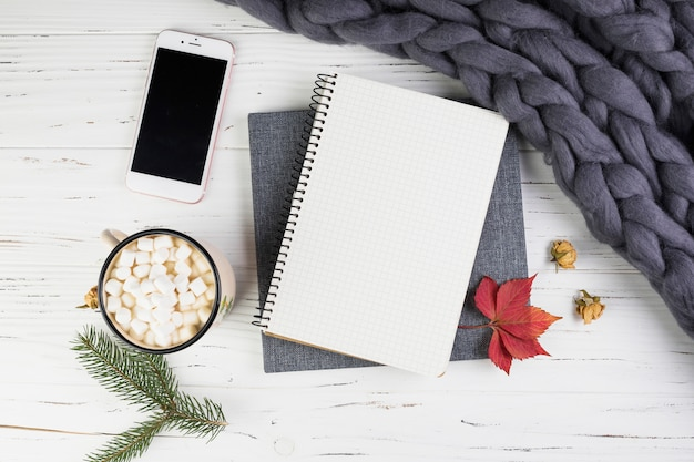 Smartphone near fir branch, cup with marshmallows and notebook Free Photo