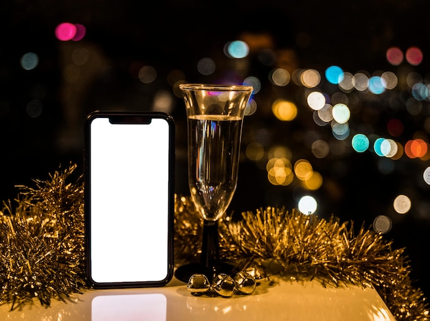 Smartphone near glass of drink and tinsel Free Photo