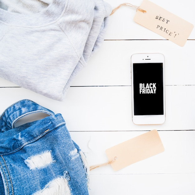 Smartphone near jean cloth and sweater with tags Free Photo