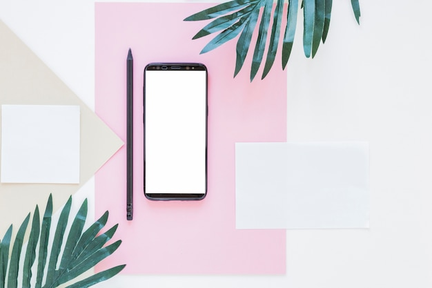Smartphone near papers and palm trees on white desk Free Photo