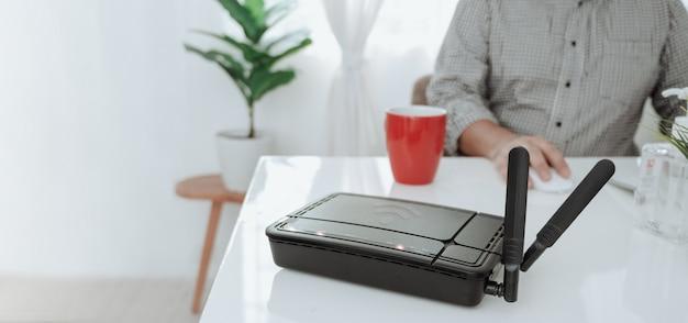 Крупный план беспроводного маршрутизатора и человека используя smartphone на ofiice живущей комнаты дома. Premium Фотографии