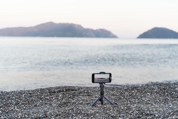 一脚スティック上のスマートフォン。海の夕日のビデオを記録。コンテンツクリエータ Premium写真