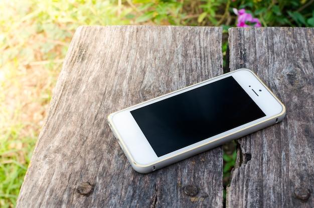 Смартфон на старом коричневом деревянном фоне в саду Premium Фотографии