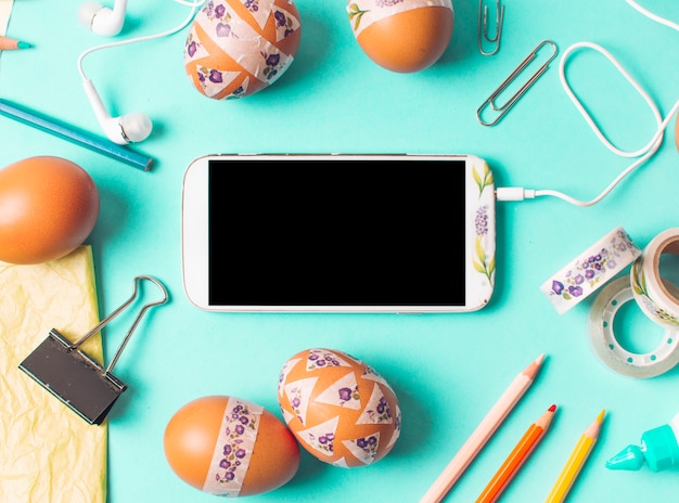 Smartphone between set of brown chicken eggs and stationery Free Photo
