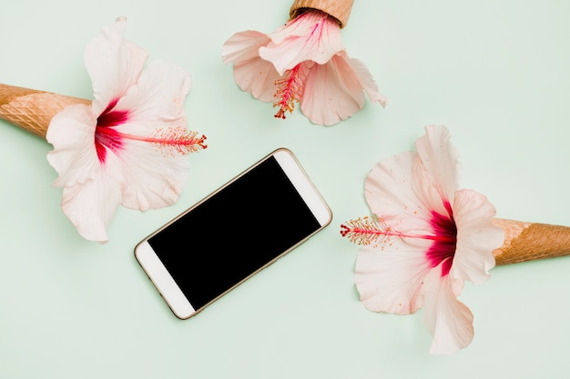 Smartphone surrounded with hibiscus flowers in waffle cones against colored backdrop Free Photo