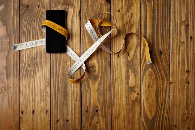 소박한 나무 테이블 상단보기에 제시된 조정 미터에 묶인 스마트 폰 무료 사진