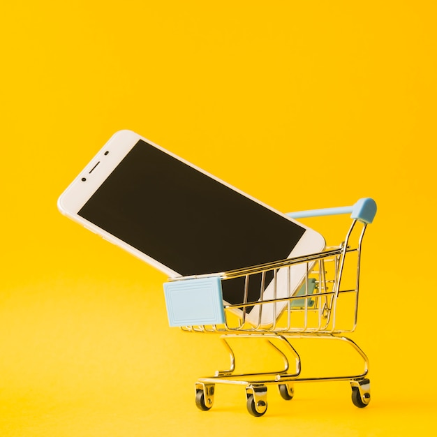 Smartphone in toy supermarket cart Free Photo