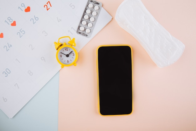 Smartphone to track your menstrual cycle and for marks. pms and the critical days concept. cotton tampon, daily pad and yellow alarm on the pink background. Premium Photo