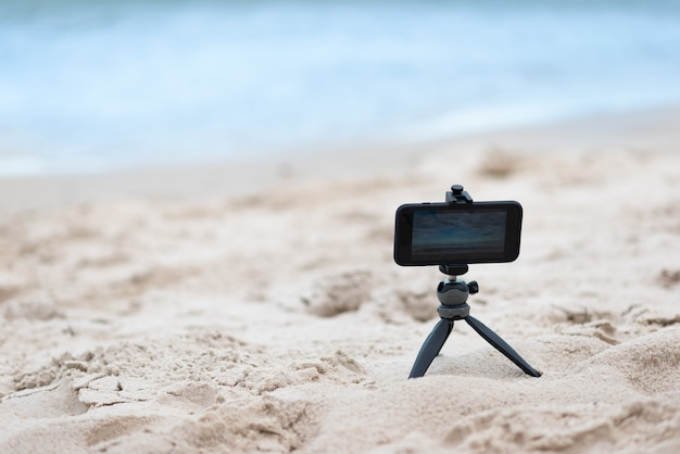 Smartphone on tripod on sand and sea background Premium Photo