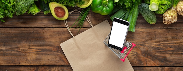 Smartphone with green vegetables on wooden table with shopping trolley. food ordering through mobile cell phone application concept Premium Photo