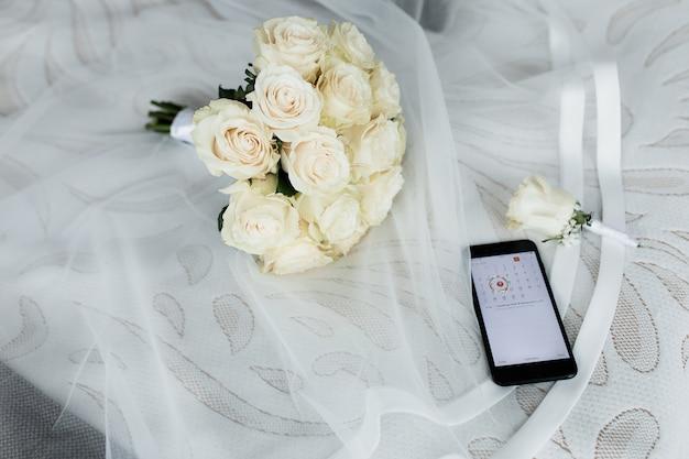 開いたカレンダー、結婚式のボタンホール、ベールに白いバラのウェディングブーケを持つスマートフォン 無料写真