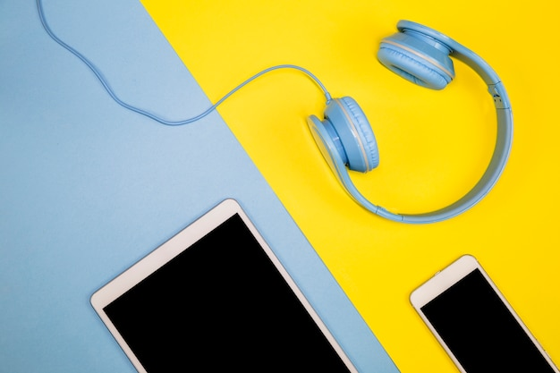 Smartphone with tablet and headphones on table Free Photo